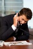 Geschäftsmann, der am Telefon in einem Büro schreit Stockfoto
