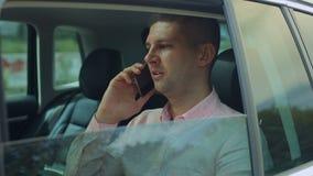 Geschäftsmann, der am Telefon im Rücksitz des Autos spricht stock video