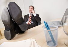 Geschäftsmann, der am Telefon mit Füßen oben spricht Stockfotografie