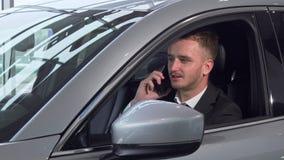Geschäftsmann, der am Telefon, sitzend in einem neuen Automobil spricht stock footage