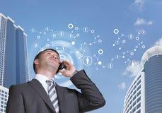 Geschäftsmann, der am Telefon spricht Wolkenkratzer und Lizenzfreie Stockbilder