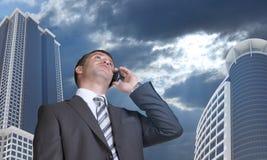 Geschäftsmann, der am Telefon spricht Wolkenkratzer und Lizenzfreies Stockfoto