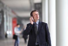 Geschäftsmann, der am Telefon während einer Dienstreise spricht Stockbild