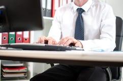 Geschäftsmann, der an Tischrechner arbeitet Lizenzfreies Stockbild
