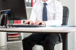 Geschäftsmann, der an Tischrechner arbeitet Stockfoto