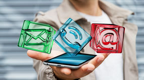 Geschäftsmann, der transparente Würfelkontaktikone über Telefon, 3D hält Lizenzfreies Stockbild