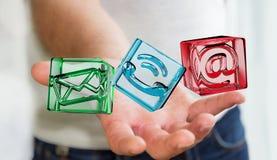 Geschäftsmann, der transparente Würfelkontaktikone in seiner Hand 3D hält Stockbild