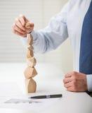 Geschäftsmann, der Turm von den Holzklötzen macht Lizenzfreies Stockfoto