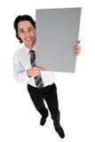Geschäftsmann, der unbelegtes Plakat anhält stockbild