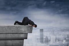 Geschäftsmann, der unten von der Dachspitze schaut Lizenzfreies Stockfoto