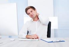 Geschäftsmann, der unter den Schmerz leidet Stockbild