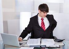 Geschäftsmann, der unter Rückenschmerzen am Schreibtisch leidet Stockfotografie