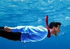 Geschäftsmann, der unter Wasser schwimmt lizenzfreie stockfotos