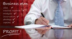Geschäftsmann, der am Unternehmensplan arbeitet Lizenzfreies Stockbild