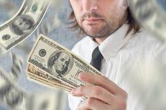 Geschäftsmann, der US-Dollars, bnknotes fallen vom Himmel hält Stockfoto