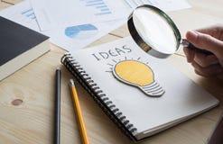 Geschäftsmann, der Vergrößerungsglas mit Glühlampe hält steigendes Diagramm auf Kreidebrett Lizenzfreie Stockbilder