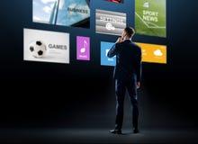 Geschäftsmann, der virtuelle Anwendungen betrachtet stockbilder