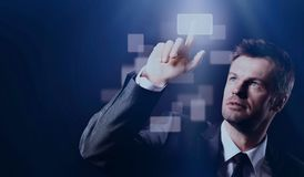 Geschäftsmann, der virtuellen Knopf auf schwarzem Hintergrund bedrängt stockfotos