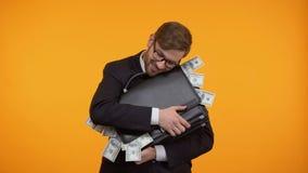 Geschäftsmann, der voll Aktenkoffer Geld, lokalisiert auf gelbem Hintergrund umarmt stock footage