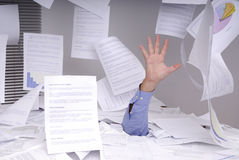 Geschäftsmann, der voll in einem Schreibtisch der Papiere ertrinkt Stockfoto