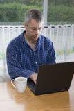 Geschäftsmann, der vom Haus in den Pyjamas arbeitet Stockfoto
