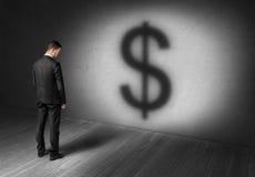 Geschäftsmann, der vor Betonmauer auf Scheinwerfer mit dem großen Dollarzeichen aussieht wie Schatten steht Stockfotografie