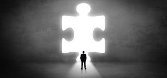 Geschäftsmann, der vor einem großen Puzzlespielstück steht lizenzfreie stockbilder