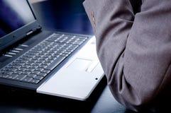 Geschäftsmann, der vor einem Laptop denkt Lizenzfreies Stockfoto