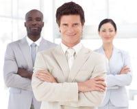 Geschäftsmann, der vor Geschäftsteam lächelt Stockbild