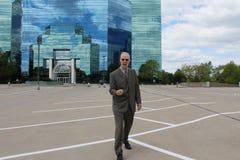 Geschäftsmann, der vor widergespiegeltem Gebäude feiert lizenzfreies stockbild