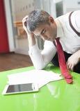 Geschäftsmann, der während einschläft, Dokumente lesend Lizenzfreies Stockbild