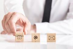 Geschäftsmann, der Würfel mit E-Mail-- und Telefonpiktogrammen setzt Stockbilder