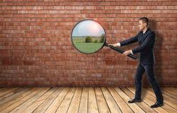 Geschäftsmann, der Wand des roten Backsteins durch ein Vergrößerungsglas betrachtet und Naturlandschaft sieht Lizenzfreie Stockbilder