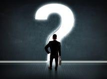 Geschäftsmann, der Wand mit einem hellen Fragezeichen betrachtet Stockbild