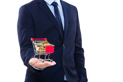 Geschäftsmann, der Warenkorb mit Goldmünze hält Lizenzfreie Stockfotos