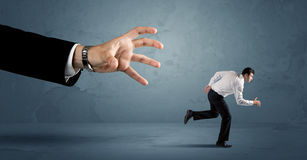 Geschäftsmann, der weg von einem Konzept der riesigen Hand läuft Lizenzfreies Stockbild