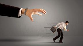 Geschäftsmann, der weg von einer riesigen Hand läuft Stockbild