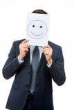 Geschäftsmann, der weiße Karte mit Gesicht auf ihm hält Lizenzfreie Stockfotografie