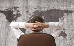 Geschäftsmann, der Weltkarte betrachtet Stockbilder