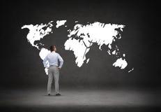 Geschäftsmann, der Weltkarte betrachtet Stockfotos