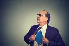 Geschäftsmann, der wie ein Superheld fungiert und sein Hemd auseinander reißt lizenzfreies stockbild