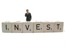 Geschäftsmann, der wo man denkt, investiert Stockfotos