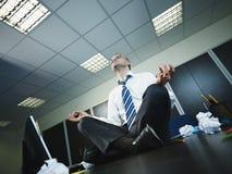 Geschäftsmann, der Yoga im Büro tut lizenzfreies stockfoto