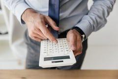 Geschäftsmann, der Zählungen auf Taschenrechner in den Händen macht Stockfotografie