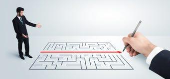 Geschäftsmann, der Zeichnungslösung zur Hand nach Labyrinth sucht Lizenzfreie Stockfotos