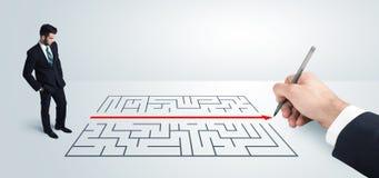 Geschäftsmann, der Zeichnungslösung zur Hand nach Labyrinth sucht Stockfotografie