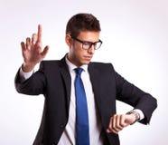 Geschäftsmann, der Zeit überprüft und Taste eindrückt Stockfoto
