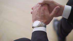 Geschäftsmann, der Zeit auf seiner Armbanduhr überprüft Mann, der an Hand Uhr setzt Pflegen Sie fertig morgens werden vorher stock video footage