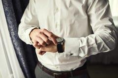 Geschäftsmann, der Zeit auf seiner Armbanduhr, Mann an Hand setzt Uhr, Bräutigam morgens wird fertig vor Hochzeitszeremonie überp stockbild