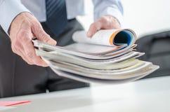 Geschäftsmann, der Zeitschriften hält lizenzfreie stockbilder